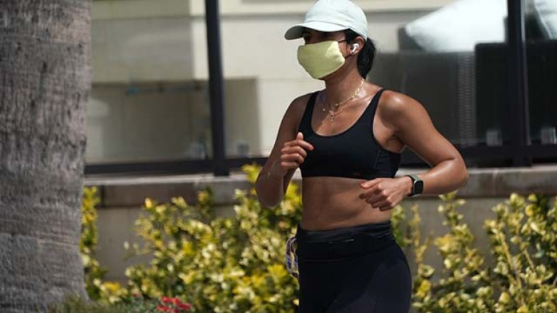 A jogger wears a mask adjacent to the beach in La Jolla.